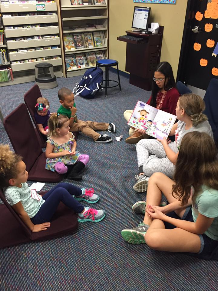 Middle-schoolers reading to small children
